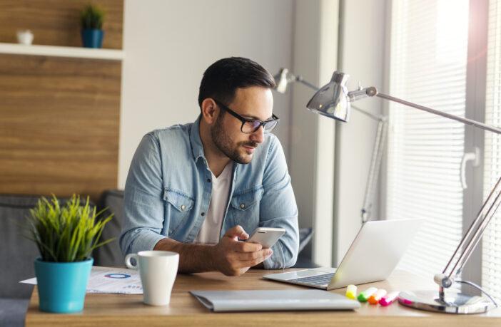 Junger Mann arbeitet zu Hause am Laptop im Homeoffice